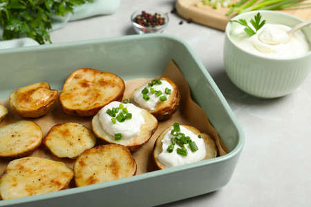 Sour cream and delicious potato wedges on light grey table