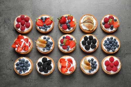 Different berry tarts on grey table, flat lay. Delicious pastries