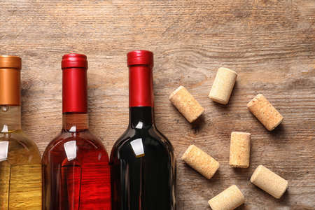 Flat lay composition with bottles of wine and corks on wooden table Stok Fotoğraf - 130043025