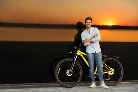 Handsome young man with bicycle near glass building at sunset. Space for text