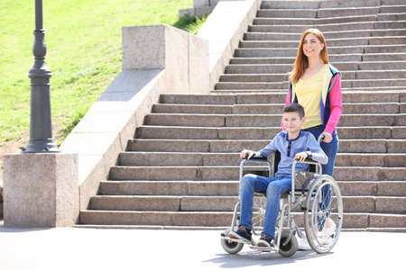 Preteen boy in wheelchair with his mother outdoors Фото со стока