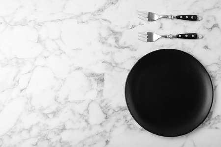 Forks and empty plate on marble table, flat lay with space for text