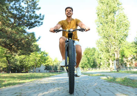 Handsome young man with bicycle in city park, low angle view Фото со стока - 129927263