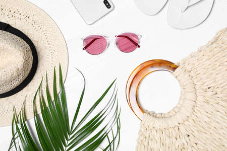 Flat lay composition with beach bag and accessories on white wooden background