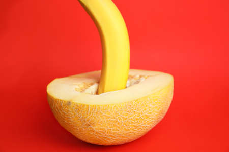 Fresh banana and melon on red background. Sex concept