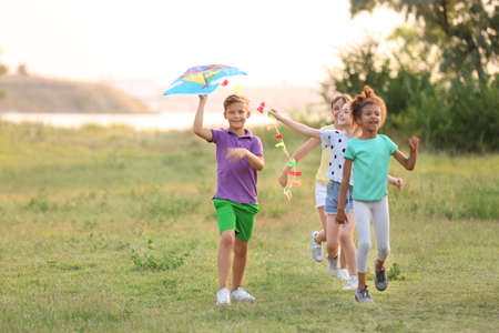 Cute little children playing with kite outdoors