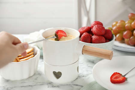 Woman dipping strawberry into fondue pot with white chocolate at marble table