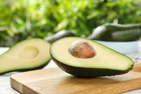 Half of delicious ripe avocado on wooden board against blurred background 版權商用圖片