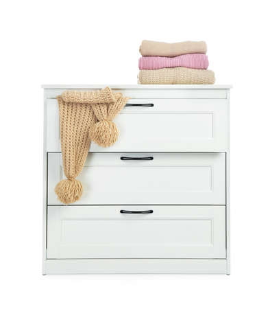 Modern wooden chest of drawers with clothes on white background