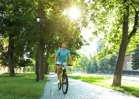 Handsome young man riding bicycle on city street Фото со стока - 129927305