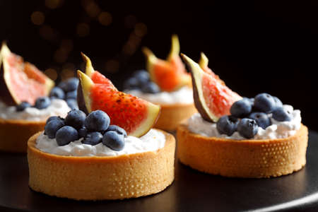 Tarts with blueberries and figs on black table against dark background, closeup. Delicious pastries Imagens