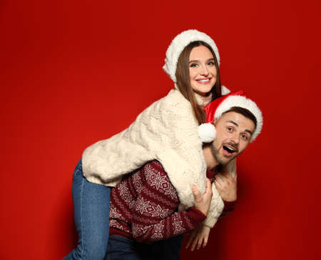 Couple wearing Christmas sweaters and Santa hats on red background 스톡 콘텐츠 - 129927309