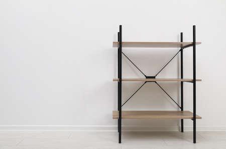 Unidad de estantes de madera moderna en la pared de luz. Espacio para texto Foto de archivo