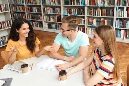 Los jóvenes discutiendo el proyecto de grupo en la mesa de la biblioteca Foto de archivo