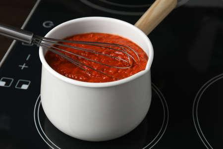Cooking delicious tomato sauce in pan on stove, closeup Foto de archivo