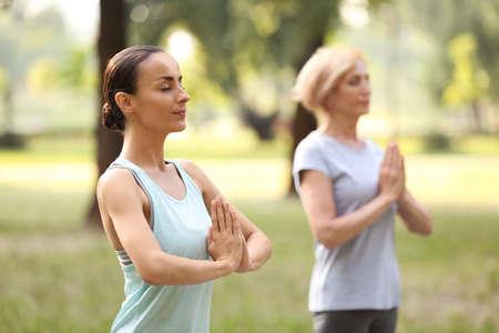 Women practicing yoga in park at morning Stockfoto
