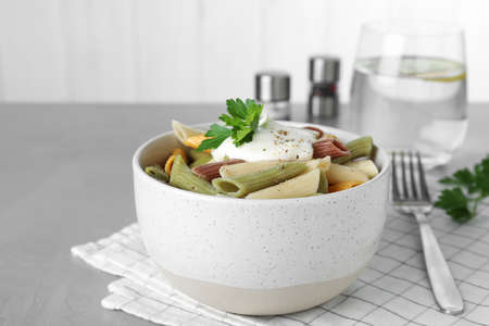 Delicious pasta with sour cream on light grey table
