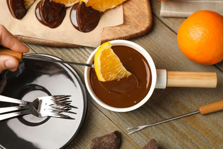 Woman dipping slice of orange into fondue pot with milk chocolate at wooden table, top view