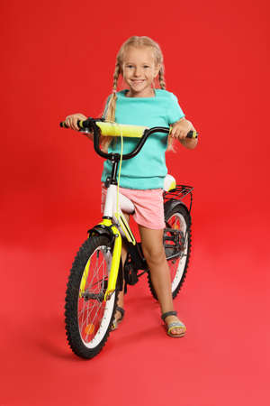 Cute little girl with bicycle on red background Фото со стока - 129927314