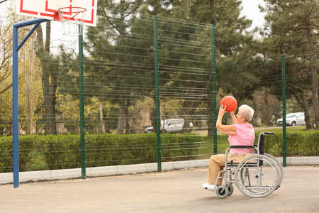 Senior woman in wheelchair playing basketball on sports ground Фото со стока - 129927342