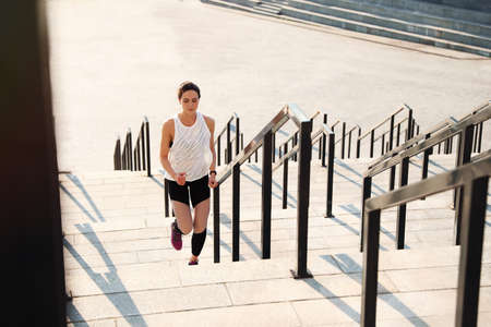 Sporty young woman running upstairs on sunny day
