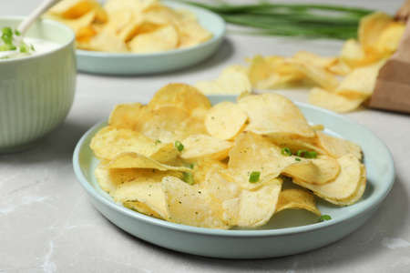 Chips and sour cream dressing on light grey table