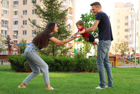 Happy family playing with adorable little baby in park