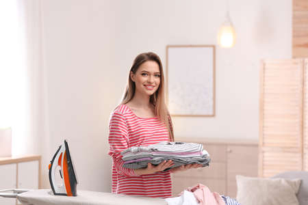 Young pretty woman holding stack of clean laundry at ironing board indoors Stock fotó