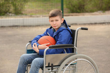 Upset boy in wheelchair with ball on sports ground Фото со стока - 129927357