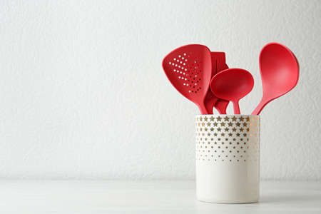 Set of kitchen utensils in stand on wooden table near light wall. Space for text