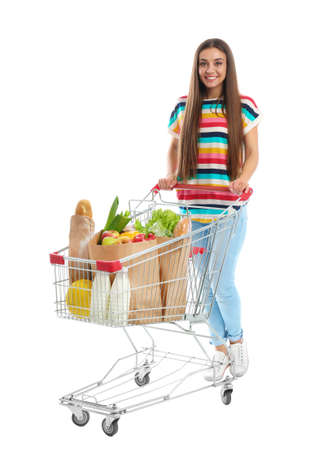 Young woman with full shopping cart on white background Foto de archivo - 129927401