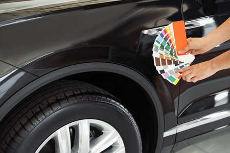 Young woman holding palette with color samples near black car, closeup 写真素材