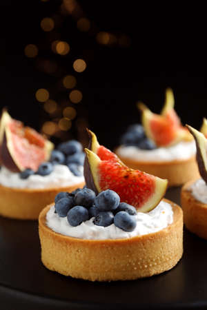 Tarts with blueberries and figs on black table against dark background, closeup. Delicious pastries Stock Photo