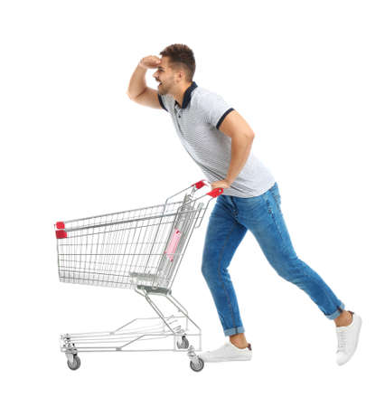 Young man with empty shopping cart on white background