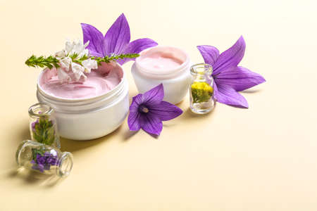 Composition with jars of body cream and flowers on beige background