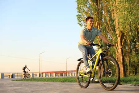 Hübscher junger Mann, der Fahrrad am Stadtufer fährt