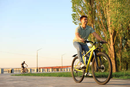 Handsome young man riding bicycle on city waterfront