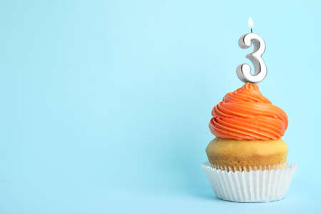 Birthday cupcake with number three candle on blue background, space for text