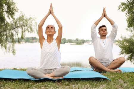 Young couple practicing yoga in park near lake at morning