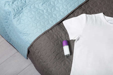 Female roll-on deodorant and white t-shirt on bed, top view. Space for text Archivio Fotografico
