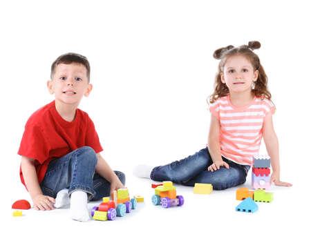 Słodkie małe dzieci bawiące się zabawkami na białym tle