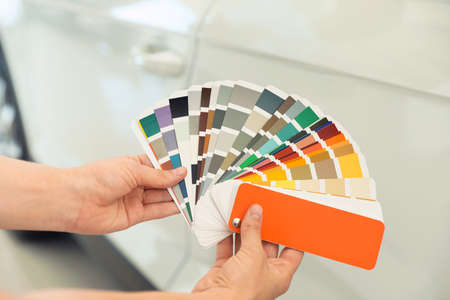 Young woman holding palette with color samples near white car, closeup