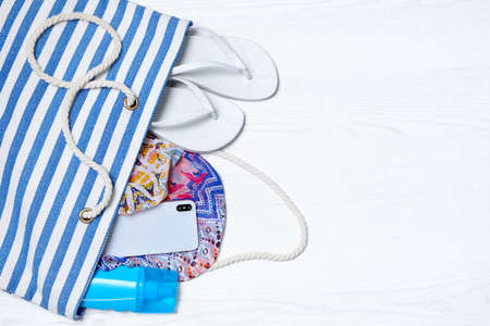 Flat lay composition with beach bag and accessories on white wooden background, space for text