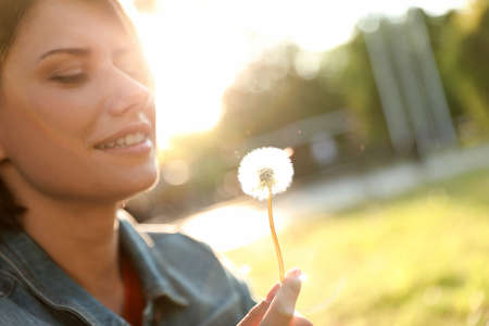 Young woman with dandelion in park on sunny day, closeup. Allergy free concept