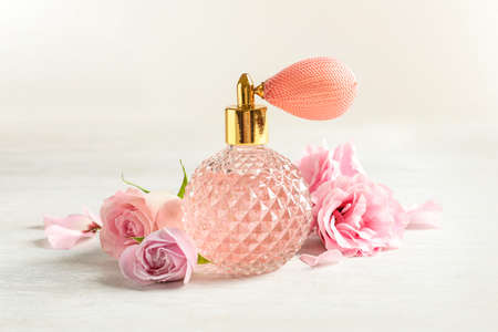 Vintage bottle of perfume and flowers on light background Foto de archivo