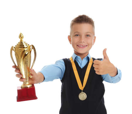 Happy boy in school uniform with golden winning cup and medal isolated on white