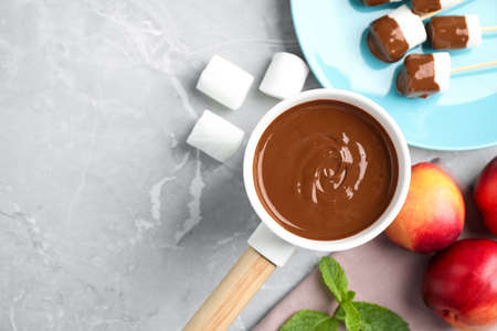 Fondue pot and marshmallow dipped into milk chocolate on light table, flat lay. Space for text