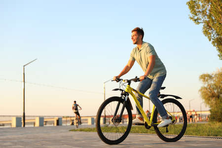Handsome young man riding bicycle on city waterfront Imagens