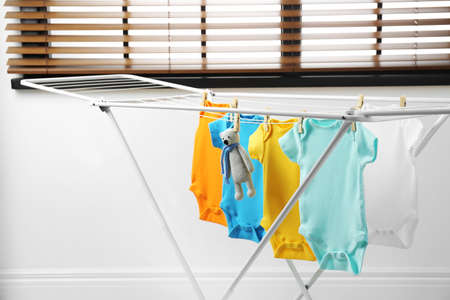 Different cute baby clothes and toy bear hanging on clothes line. Laundry day