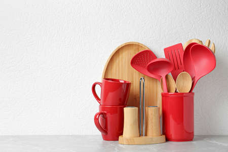 Set of kitchen utensils in stand on stone table near light wall. Space for text